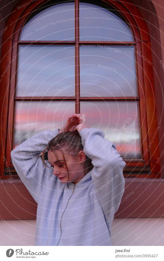 Junge Frau steht mit Händen über dem Kopf vor einem Altbau Fenster, in dem sich der Sonnenuntergang spiegelt Jugendliche Zopf Haare & Frisuren Fashion stylisch