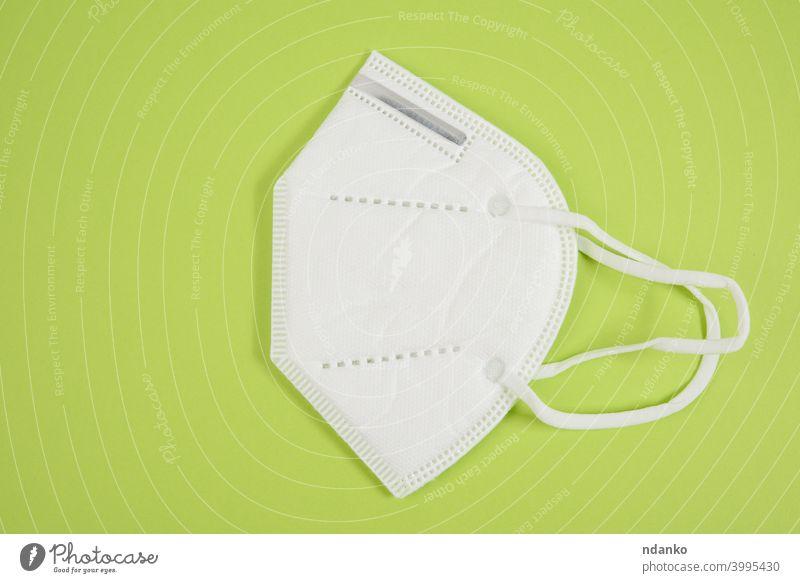 weiße medizinische Einwegmaske auf grünem Hintergrund, persönliche Schutzausrüstung Mundschutz Medizin Pandemie Lungenentzündung Prävention schützend Quarantäne