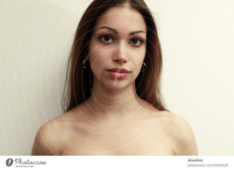 Porträt einer jungen, schönen, brünetten Frau vor einer hellen Wand Junge Frau hübsch langhaarig schlank Teenager 18-25 Jahre Jugendliche ästhetisch Identität