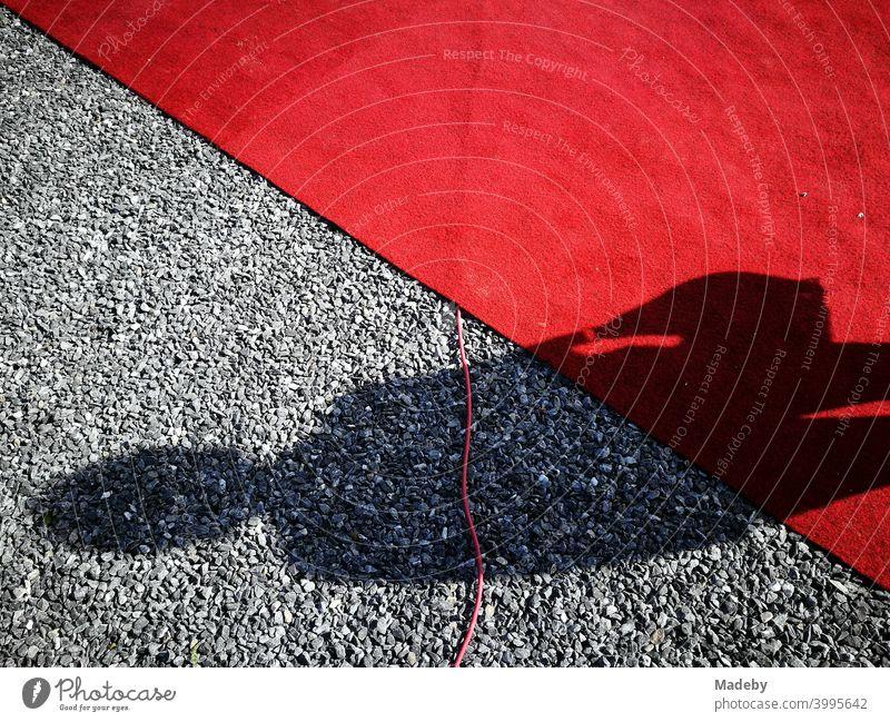 Schatten einer Frau mit Handtasche auf rotem Teppich und grauen Kieselsteinen bei einer Vernissage in Oelde bei Warendorf in Westfalen Roter Teppich Knallrot