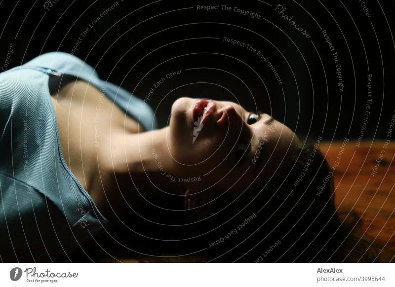 Porträt einer jungen schönen brünetten Frau, die auf einem Holztisch in einem dunklen Raum liegt und nach oben schaut Junge Frau hübsch langhaarig schlank