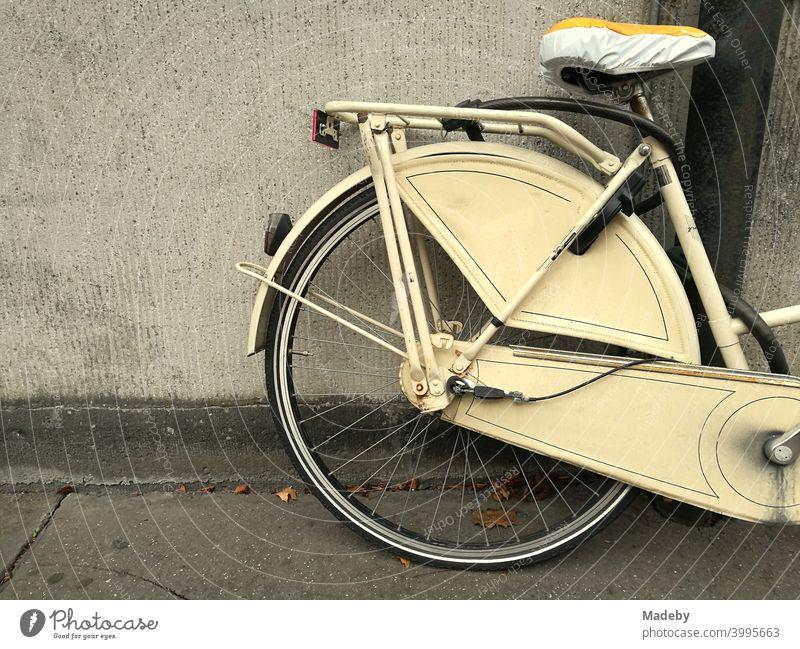 Klassisches Hollandrad in Beige mit Sattelschoner vor farblich passender Hauswand in Köln am Rhein in Nordrhein-Westfalen Rad Fahrrad Damenrad Mantelschutz