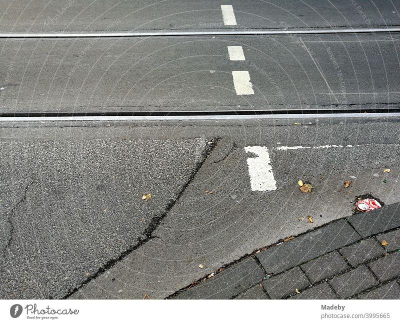 Alter grauer Asphalt mit Straßenbahnschienen und weißer Markierung eines Fußgängerüberweg in Köln am Rhein in Nordrhein-Westfalen Fahrbahn Schiene Verkehr
