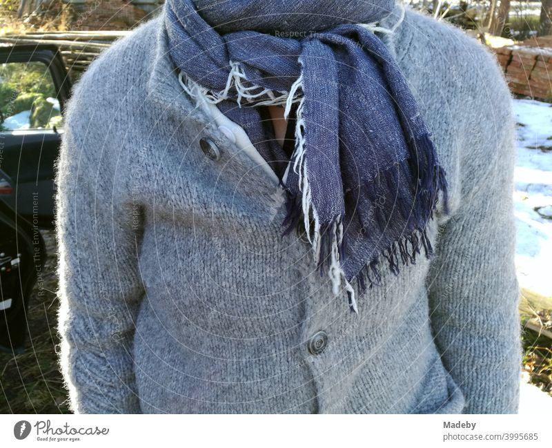 Rustikal gekleidete Frau mit grauer Wolljacke und blauem Schal mit Fransen im Herbst vor einem Bauernhof in Rudersau bei Rottenbuch im Kreis Weilheim-Schongau in Oberbayern
