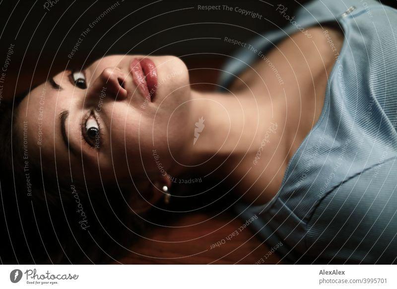 Porträt einer jungen schönen brünetten Frau, die in einem dunklen Raum auf einem Holztisch liegt und nach oben schaut Junge Frau hübsch langhaarig schlank
