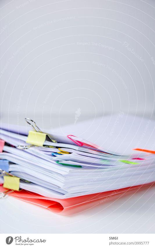 Nahaufnahme eines Satzes von Blättern, die mit Clips und Klammern befestigt sind. Vertikale Fotografie. Konzept der Informationsüberlastung überladen Stress