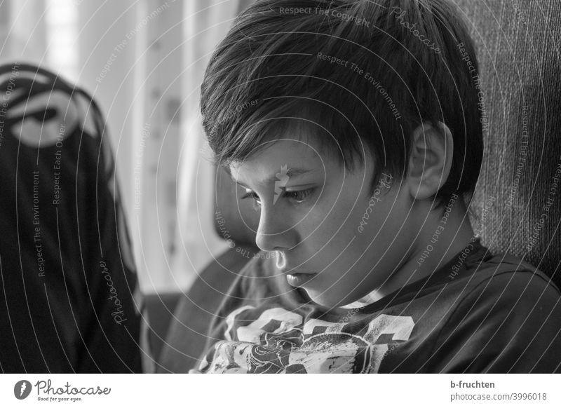 Kind sitzt auf der Couch mit Blick auf das Smartphone Junge Porträt Kindheit Gesicht Auge Haare & Frisuren Spielen Sofa sitzen bequem Schwarzweißfoto Kopf Ruhe