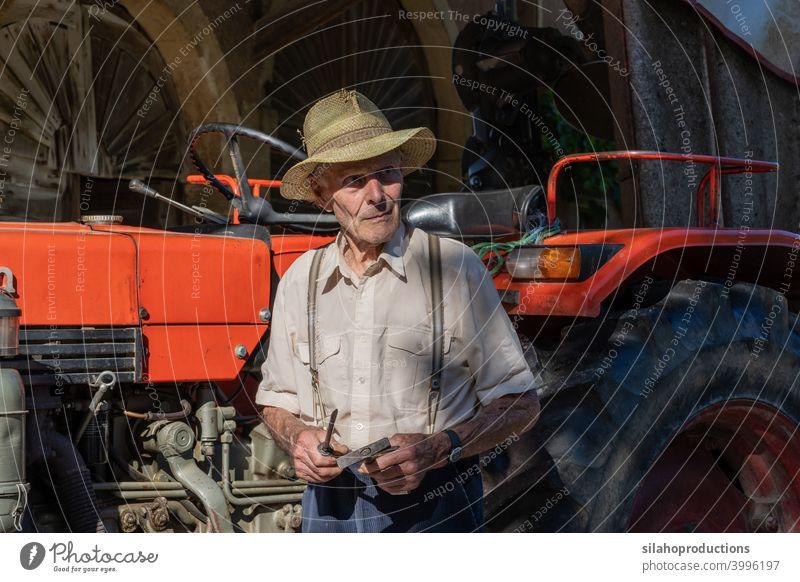 Alter Bauer arbeitet am roten Traktor unter dem Dach des Bauernhauses im Sonnenschein. Erwachsener gealtert Ackerbau Auto Automobil PKW Kaukasier Schriftzeichen