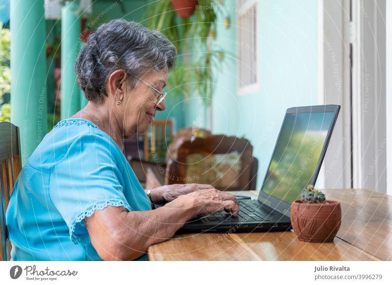 Ältere Frau bei der Arbeit mit einem modernen Laptop Sitzen Ruhestand Erwachsener Computer Technik & Technologie im Innenbereich alt Frauen Tippen Beteiligung