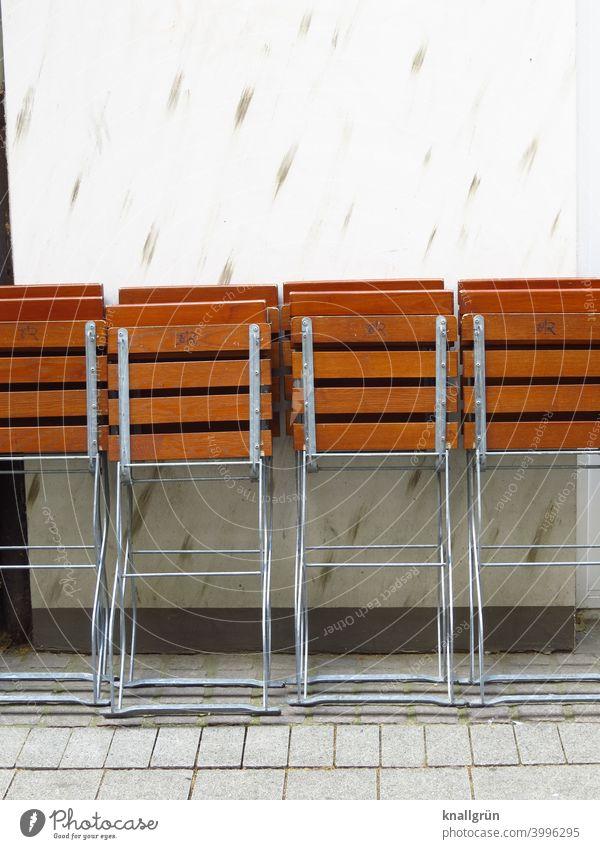 Zusammengeklappte Biergartenstühle vor geschlossener Gastronomie Klappstuhl Stuhl Restaurant Straßencafé Café Menschenleer Außenaufnahme Sitzgelegenheit