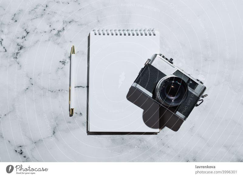 Flatlay von Vintage-Filmkamera und Notizbuch mit Stift auf Marmor Notebook retro Fotokamera Filmmaterial altehrwürdig Draufsicht Business Tisch heimwärts