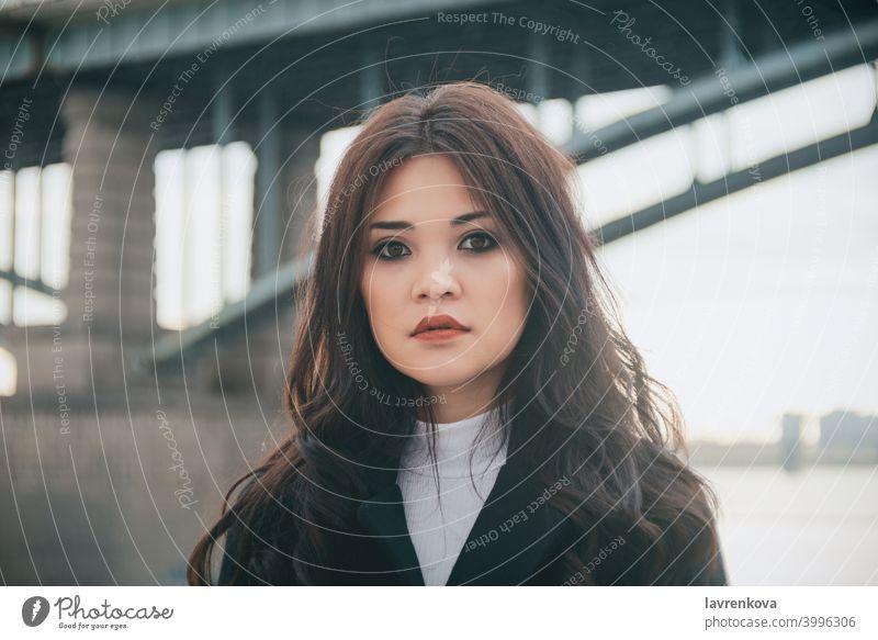 Porträt der asiatischen Frau vor der Brücke bei kaltem Schönwetter Mädchen Vielfalt hübsch Mantel Behaarung im Freien allein Herbst fallen Winter saisonbedingt