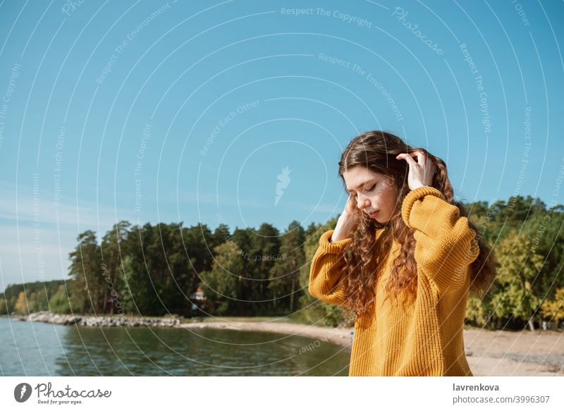 Weiblich in einem gelben Pullover stehend an einem Strand vor dem Wasser MEER Frau Meer reisen Urlaub Mädchen Feiertag jung Ausflug Rückseite Sommer Paradies