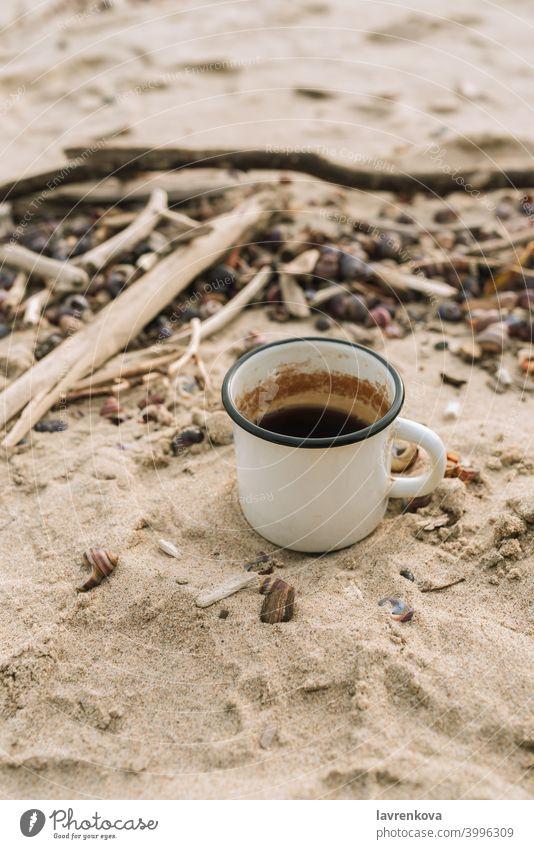 Emaille-Becher mit Heißgetränk stehend im Sand an einem wilden Strand Tasse Picknick Herbst Tee kalt Stillleben Getränk trinken heiß Metall Flucht