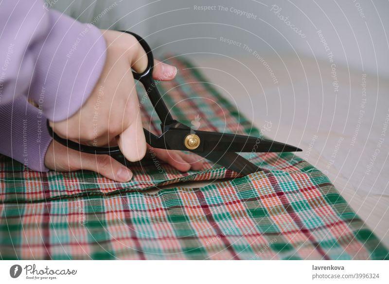 Nahaufnahme von Frau Hände halten Schere und Schneiden karierten Stoff für das Nähen Kleidung Näherin Gewebe Textil ausschneidend Beruf Schneider Werkstatt