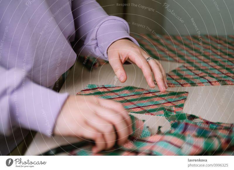 Nahaufnahme einer Schneiderin, die mit einem Papiermuster karierten Stoff ausschneidet, um ein Hemd herzustellen Gewebe Schneidern Frau Nähen Plaid Schneiden