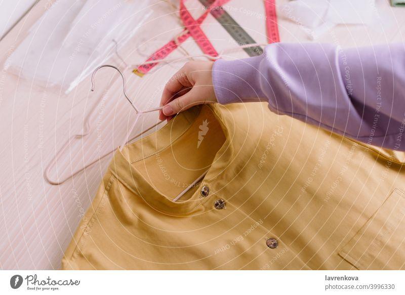 Draufsicht auf die Hände einer Näherin, die ein fertiges gelbes Hemd auf einem Bügel hält Werkstatt Job Kleiderbügel Unternehmer Frau Mädchen Schneider Nähen