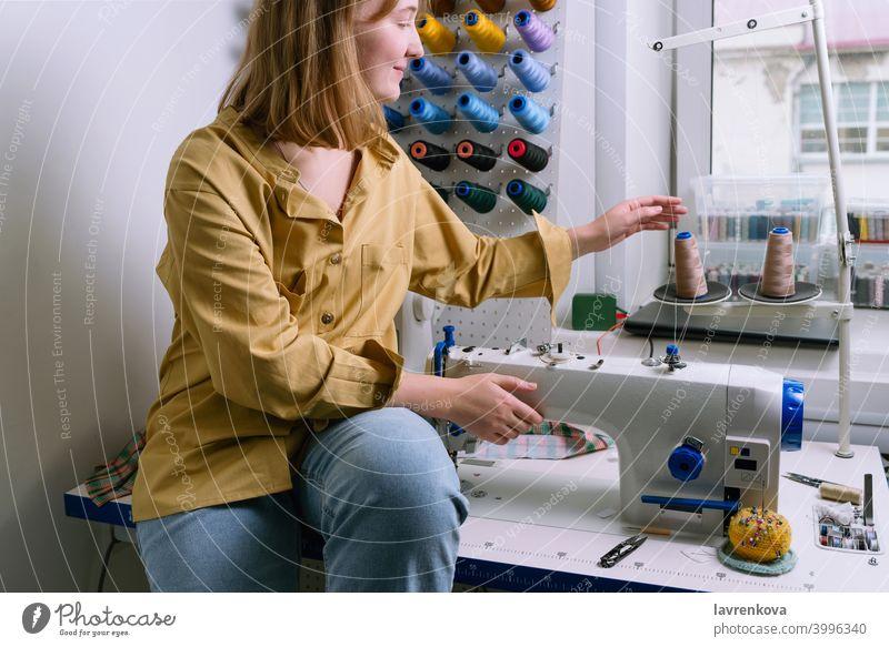 Junge Frau in gelbem Hemd sitzt in ihrer Nähwerkstatt vor den bunten Fäden und der Nähmaschine Näherin Maschine Textil Schneider Overlock Gewinde Werkstatt