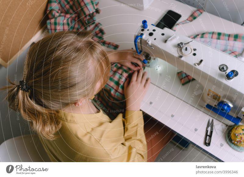 Draufsicht auf eine Frau bei der Arbeit mit der Nähmaschine in ihrer Werkstatt Maschine Nähen Gewebe Schneider Material Näherin Bekleidung Nadel Handwerk Faser