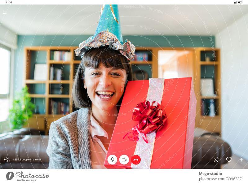 Frau feiert ihren Geburtstag online zu Hause. heimwärts virtuell Feier Mitteilung Internet soziale Distanzierung Anschluss feiern Videoanruf Geschenkverpackung