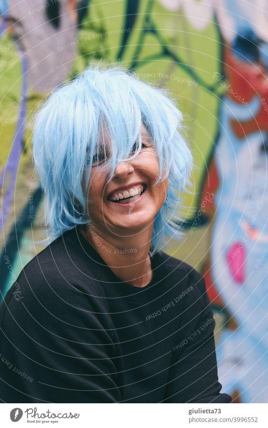 Porträt einer fröhlich, lachenden Frau / Künstlerin mit blauen Haaren Blick in die Kamera Vorderansicht Oberkörper Zentralperspektive Schwache Tiefenschärfe