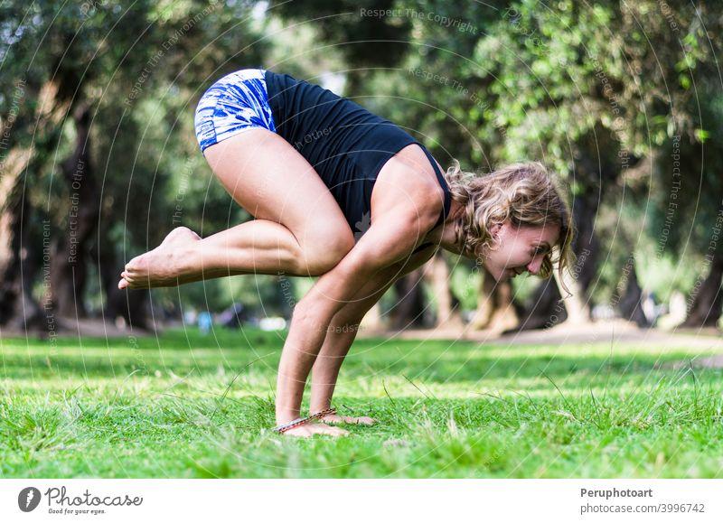 Yoga im Park, mittlere Alter Frau tun bakasana Übung Kranich Pose. Erwachsener Gleichgewicht schön Körper Kaukasier Konzentration Fitness Gras Gesundheit