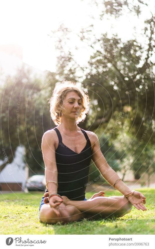 Frau meditiert und übt Yoga, Padmasana. Meditation auf sonnigen Herbsttag im Park. Workout im Freien. Aktivität Asana Übung Mädchen Gesundheit Lifestyle Natur