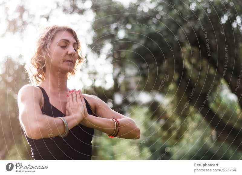 Schöne junge Frau meditiert in Yoga-Asana Padmasana - Lotus-Pose auf dem Holzdeck im Herbst Park Natur Erwachsener passen Gesundheit Lifestyle Lotos Unterlage