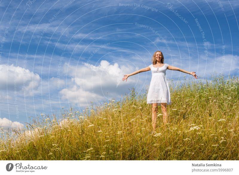 Junges Mädchen in weißem Kleid steht auf Gras Hügel auf blauem Himmel Hintergrund im Sommer Tag. jung Stehen 20s echte Menschen Wiese Freiheit im Freien Hände