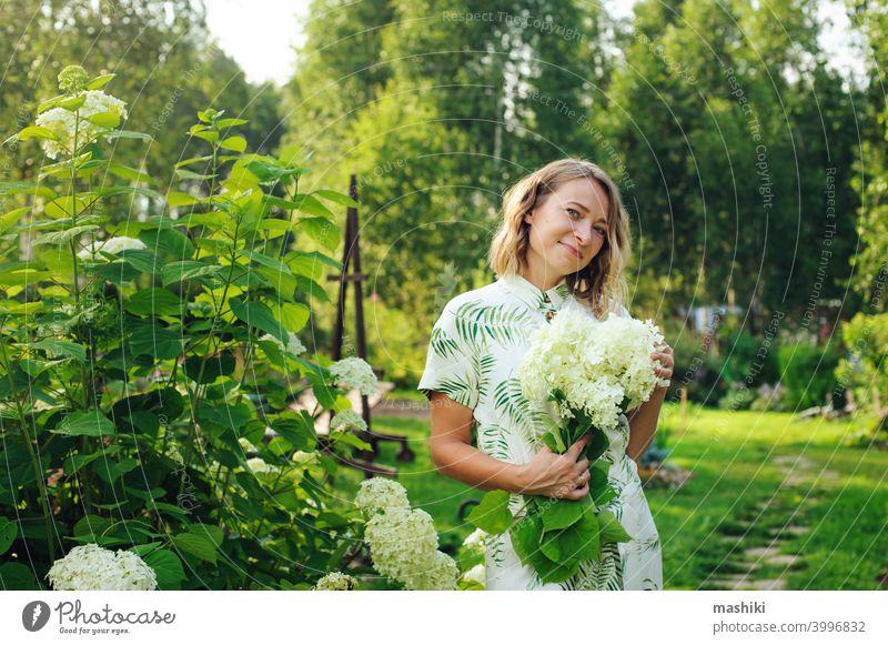 schöne junge Frau Gärtnerin posiert mit Hortensien Blumen im Sommer Hütte Garten Person Gartenarbeit im Freien Pflanze Lifestyle Natur Erwachsener Mädchen