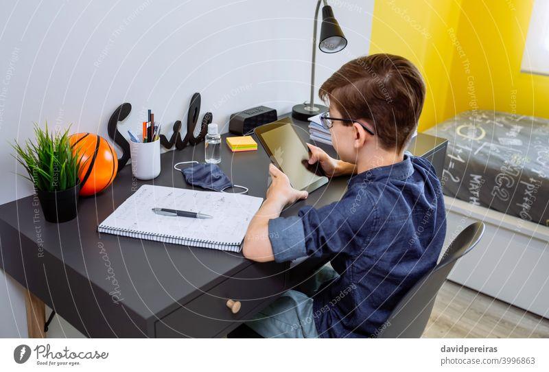 Teenager macht Hausaufgaben mit einem Tablet Tablette Schule zu Hause Coronavirus Maske auf dem Schreibtisch Flasche für Handdesinfektionsmittel Jugendzimmer
