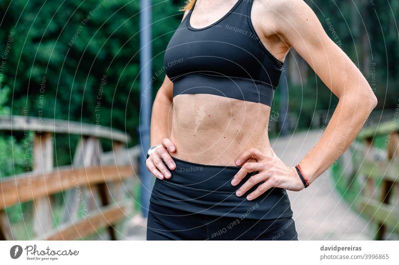 Athletin, die mit Sportbekleidung posiert. Sportlerin Mittelteil Top schlanke flacher Bauch Bauchmuskeln unkenntlich Gesundheit Frau Training Hautflecken Waffen