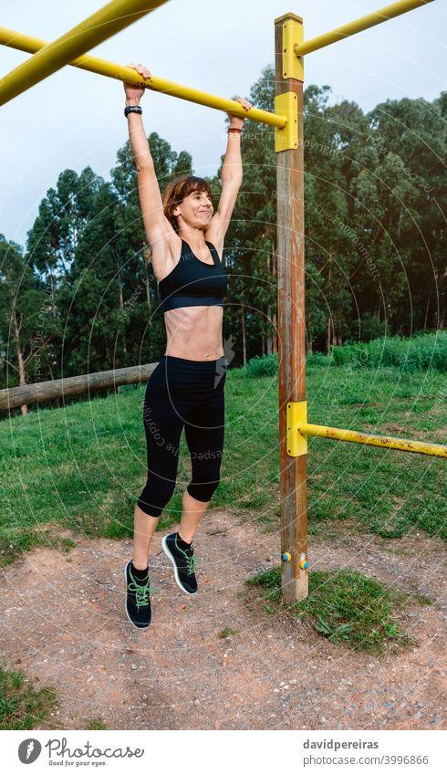Sportlerin bei Klimmzugübungen Frau Athlet erhängen Training Bar Park im Freien anstrengen Ausdauer kompetent aktiv sportlich stark Aktivität Klimmzüge