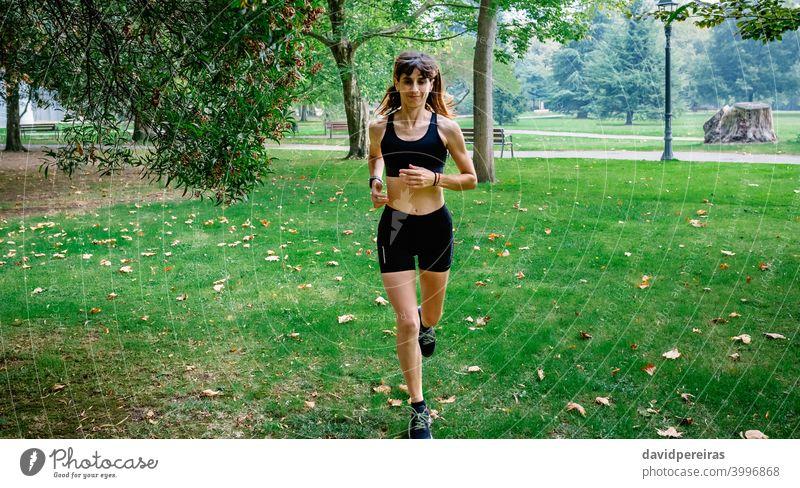 Weibliche Athletin läuft durch einen Park Läufer Frau Training Herbst Sportlerin Morgen jung Menschen passen Gesundheit Körper Übung Mädchen sportlich Fitness