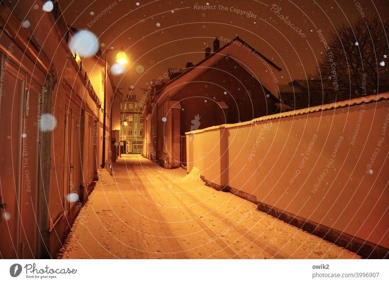 Verhüllte Gasse Stadt Kleinstadt Gebäude Schneeflocke Schneefall kalt Haus Farbfoto Straßenbeleuchtung ruhig Gedeckte Farben Menschenleer Außenaufnahme Low Key