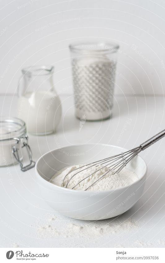 Mehl in einer Schüssel und Zutaten auf einem weißen Tisch Milch Zucker Frühstück kuchen backen Vorratsbehälter Glas Vorbereitung Teig Küche Lebensmittel