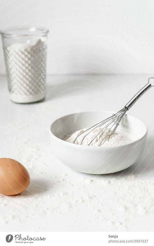 Mehl in einer Schüssel und ein Ei auf einem weißen Küchentisch backen Tisch Vorbereitung Frühstück weißer Hintergrund Nahaufnahme Teig Zutaten roh