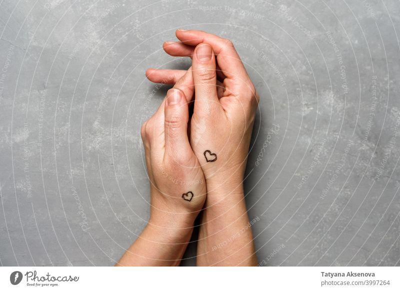 Hände mit Herzen Tattoo auf grau Valentinsgruß Hintergrund Liebe romantisch Feier Feiertag Romantik Symbol Gruß Herzform Beteiligung handpoke Paar
