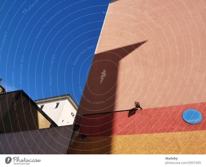 Brandmauer in Apricot mit farblich abgestimmten Streifen und blauem Punkt vor blauem Himmel bei Sonnenschein im Nordend von Frankfurt am Main in Hessen Fassade