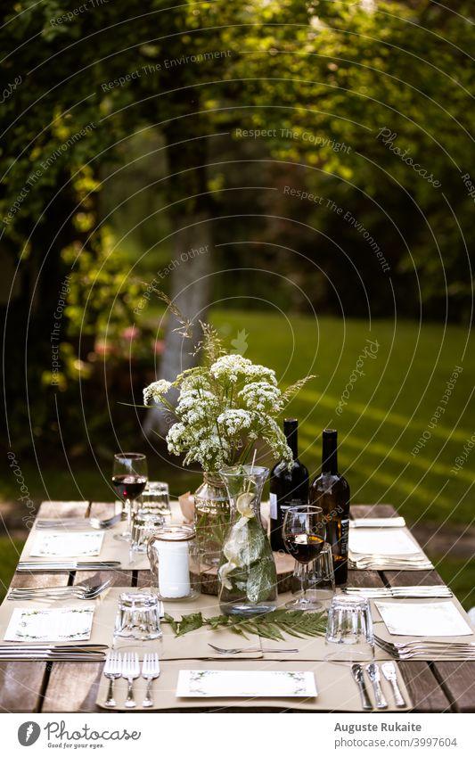 Servierter Restauranttisch im Freien Speisetafel Tisch Wein Weinglas Weinprobe Gießkanne Wasser Gabel Messer Glas Glasflasche Blumen und Pflanzen Sonnenlicht