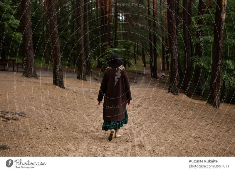 Frau zu Fuß im Wald an einem bewölkten Herbsttag Herbstlaub Mantel Hut Herbst des Lebens Herbstwetter Waldspaziergang Schneise regnerisches Wetter reine Luft