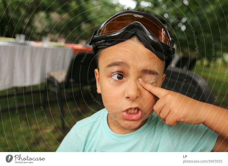 Kind macht ein Gesicht und hält den Finger auf sein Auge zögernd verwirrt ratlos skeptisch Zweifel zweifelhaft hestitate Unsicherheit Verwirrung Kindheit