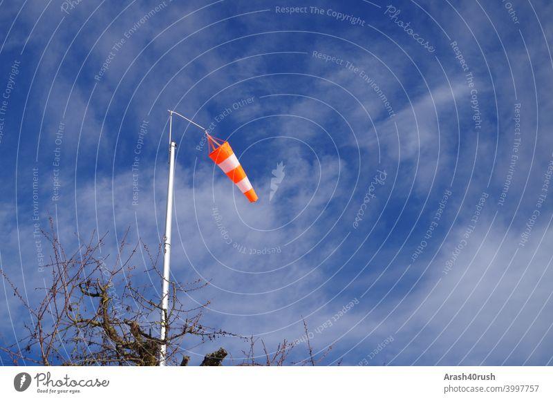Wehender Windsack bei blauen Himmel Blau Wolken Natur Outside Orange-weiss Warnung Zeichen