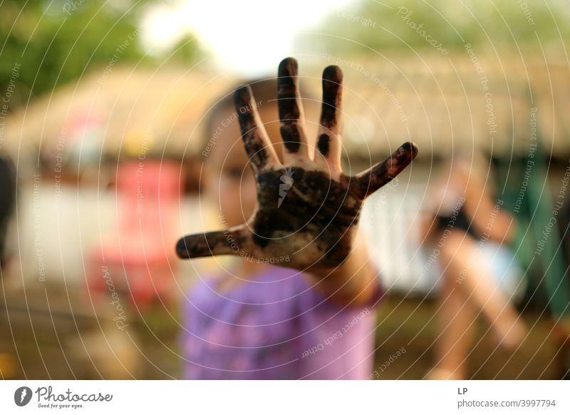 Kind zeigt eine bemalte schwarze Palme Vorderansicht Porträt Zentralperspektive Unschärfe Tag Detailaufnahme Nahaufnahme Muster unfreundlich Hautfarbe Finger