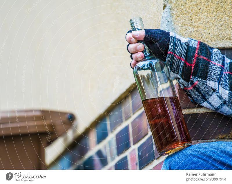 Nahaufnahme von einem anonymen Mann der an einem Gebäude sitzt und eine offene Schapsflasche in der Hand hält Alkohol Alkoholismus Sucht Mülltonne Säufer