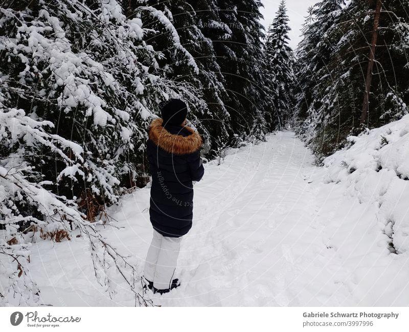 Frau bei Spaziergang im Wald mit Schnee Tannen Schwarzwald Waldweg Wintermantel Skihose Mütze Weiß schwarz braun kalte Jahreszeit frostig gefroren Zweige