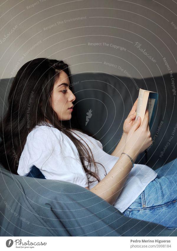 Frau lesend auf einem Sofa heimwärts Freizeit Sitzen bequem Wohnzimmer Kaukasier Lifestyle brünett im Innenbereich häusliches Leben Freizeitkleidung Glück