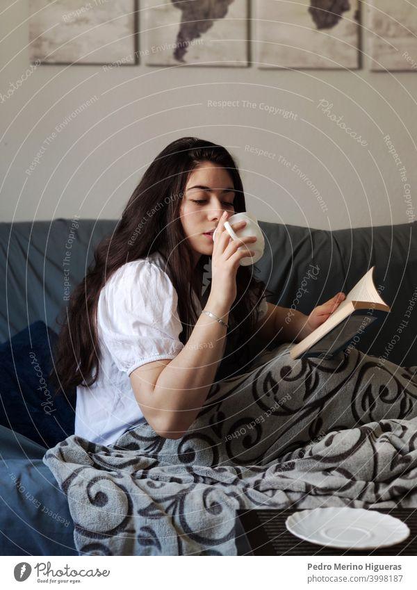 Frau trinkt aus einer Tasse Kaffee und liest ein Buch sich[Akk] entspannen warm weich niedlich ruhen schön Glück jung lebend Innenbereich Erholung Fenster