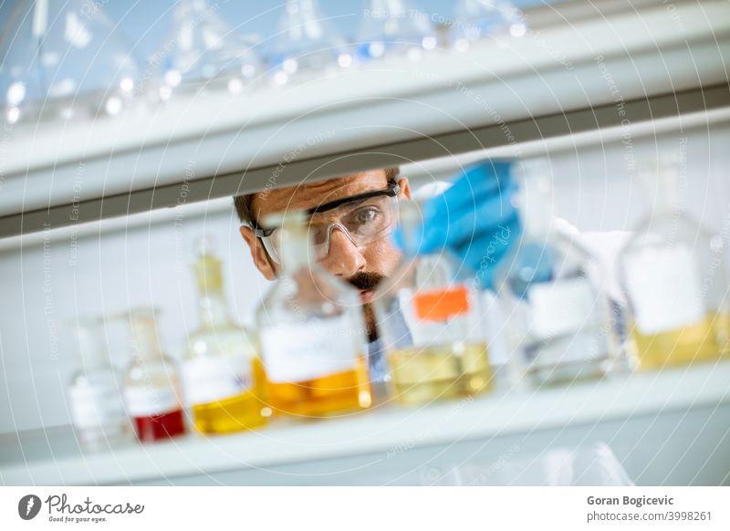 Junger Forscher mit Schutzbrille beim Prüfen von Reagenzgläsern Analyse Analysieren Biochemiker Biochemie Biologie Biotechnologie Kaukasier Chemikalie Chemiker