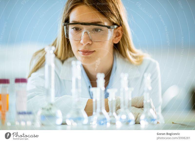 Weiblicher medizinischer oder wissenschaftlicher Forscher mit Blick auf einen Kolben mit Lösungen in einem Labor Frau Wissenschaftler forschen Experiment